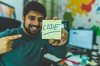 programmer smiling with code written on sticky note